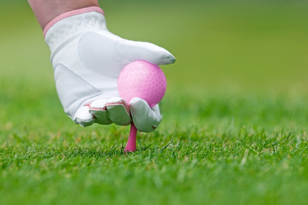 Ladies golf hand placing pink tee and ball into ground.
